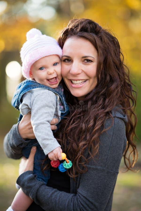 Bebé de risa de la tenencia de la mamá fotos de archivo