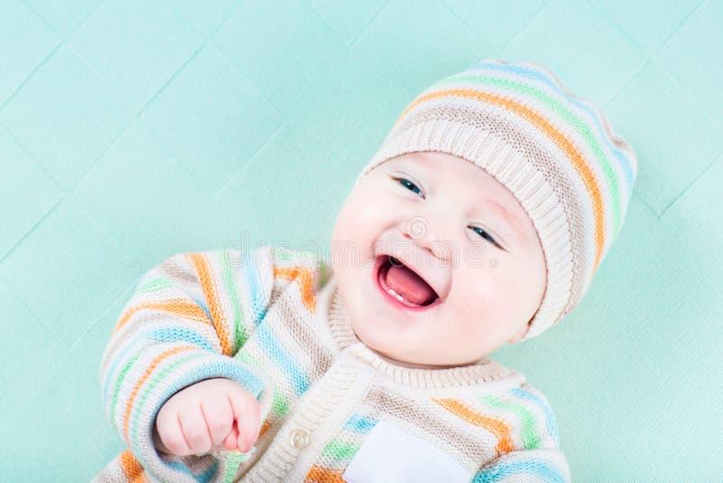 Bebé de risa que lleva la chaqueta y el sombrero knited calientes imagenes de archivo