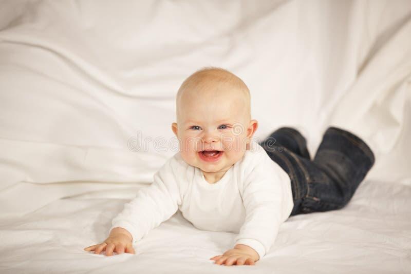 Download Bebé De Riso Que Encontra-se Em Um Sofá Foto de Stock - Imagem de felicidade, bonito: 16856812