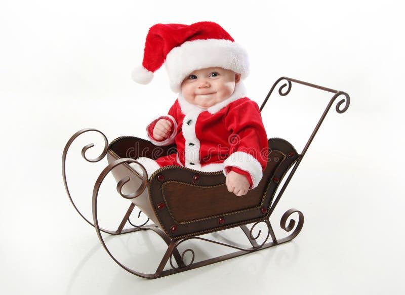 Bebé de Santa que se sienta en un trineo fotos de archivo