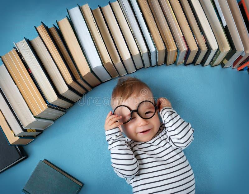 Bebé de un año con los spectackles y los libros imagen de archivo libre de regalías