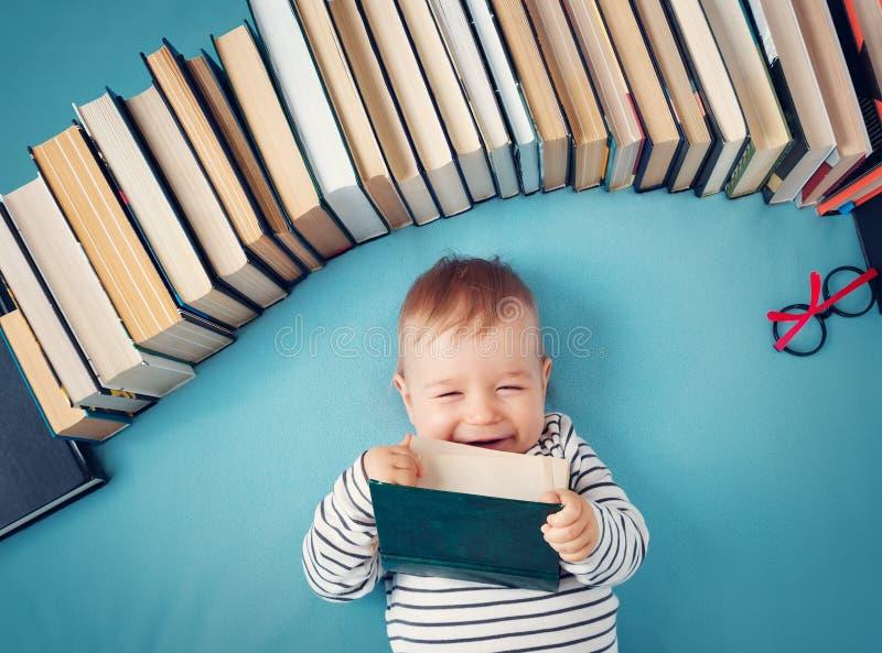 Bebé de un año con los spectackles y los libros imagen de archivo