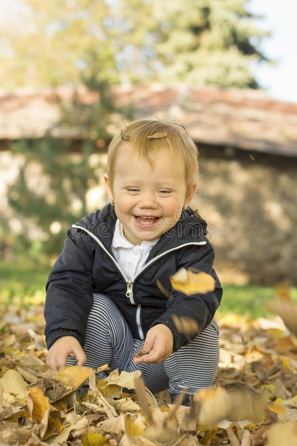 Bebé de un año lindo que juega con las hojas encendido en un parque imagenes de archivo
