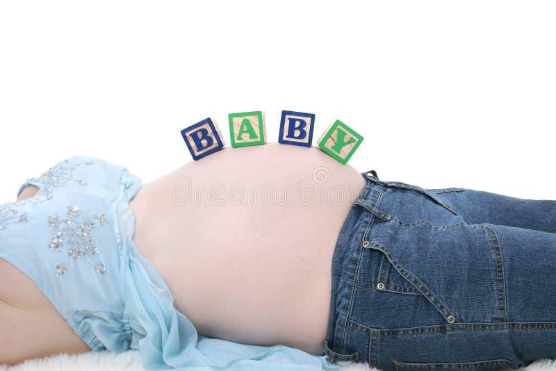 Bebé del encanto de los bloques del alfabeto a través de contar con el vientre de la mama imagen de archivo libre de regalías