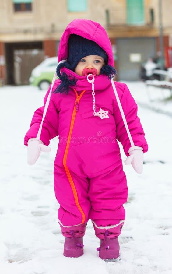 Bebé del niño en un traje magenta de la nieve que juega en la nieve imágenes de archivo libres de regalías