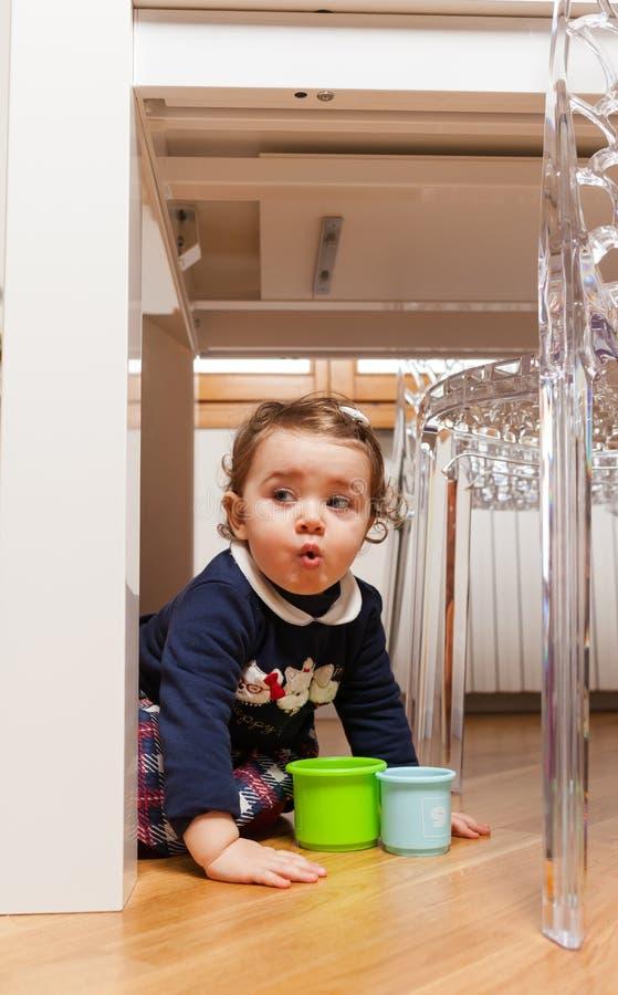 Bebé del niño que juega debajo de la tabla fotos de archivo libres de regalías