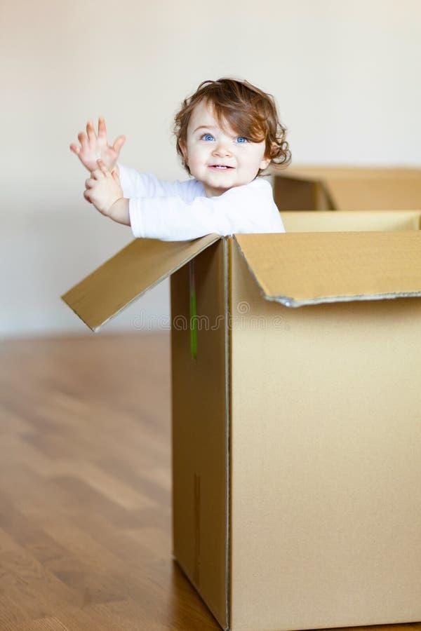 Bebé del niño que se sienta dentro de la caja de cartón marrón imagen de archivo