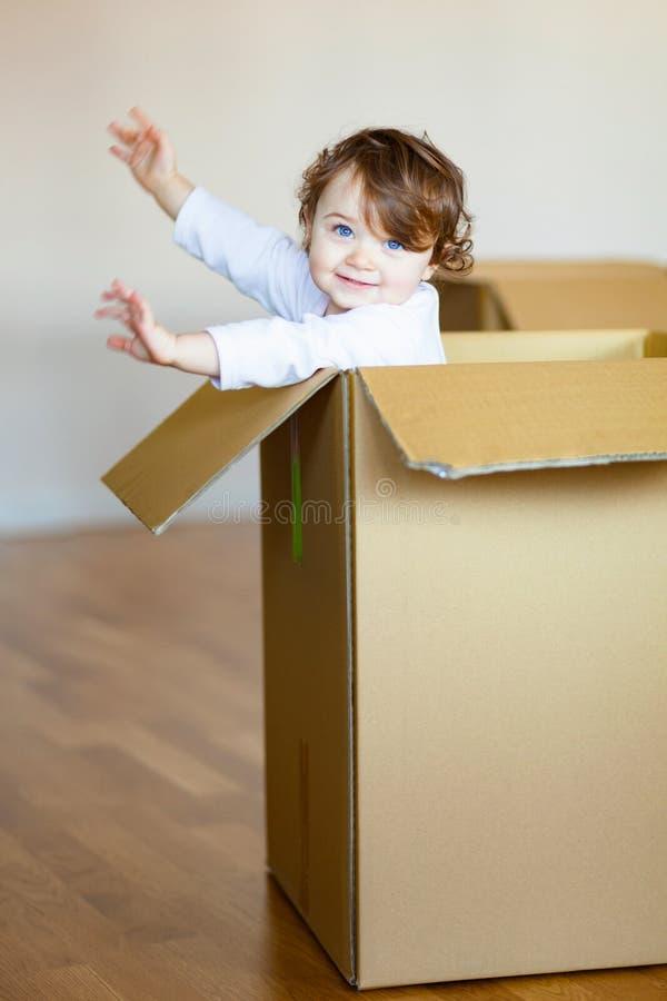 Bebé del niño que se sienta dentro de la caja de cartón marrón fotografía de archivo