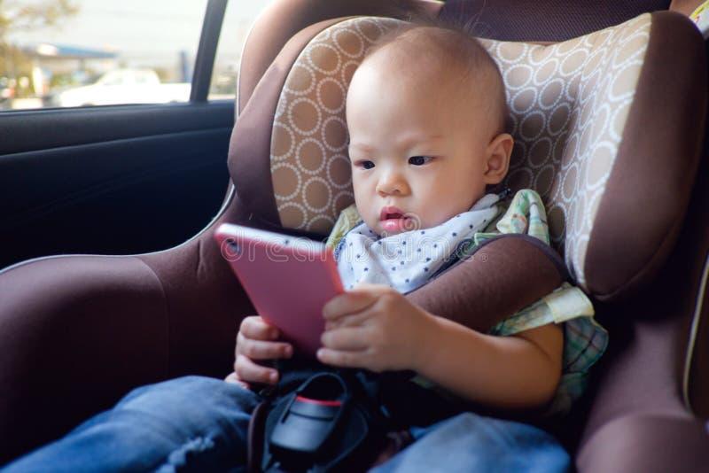 Bebé del niño que se sienta en asiento de carro y que mira un vídeo del teléfono elegante foto de archivo