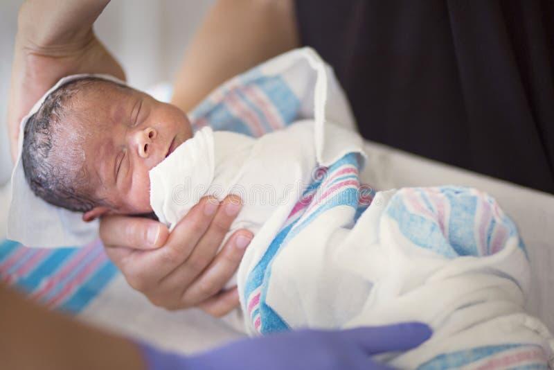 Bebé del niño recién nacido que consigue su primer baño en el hospital foto de archivo