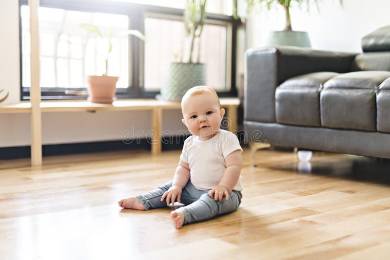 Bebé del pelirrojo sentarse en la tierra de la sala de estar fotos de archivo