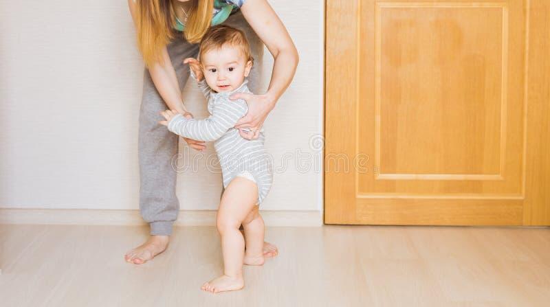 Bebé del pequeño niño que sonríe haciendo los primeros pasos imagen de archivo libre de regalías