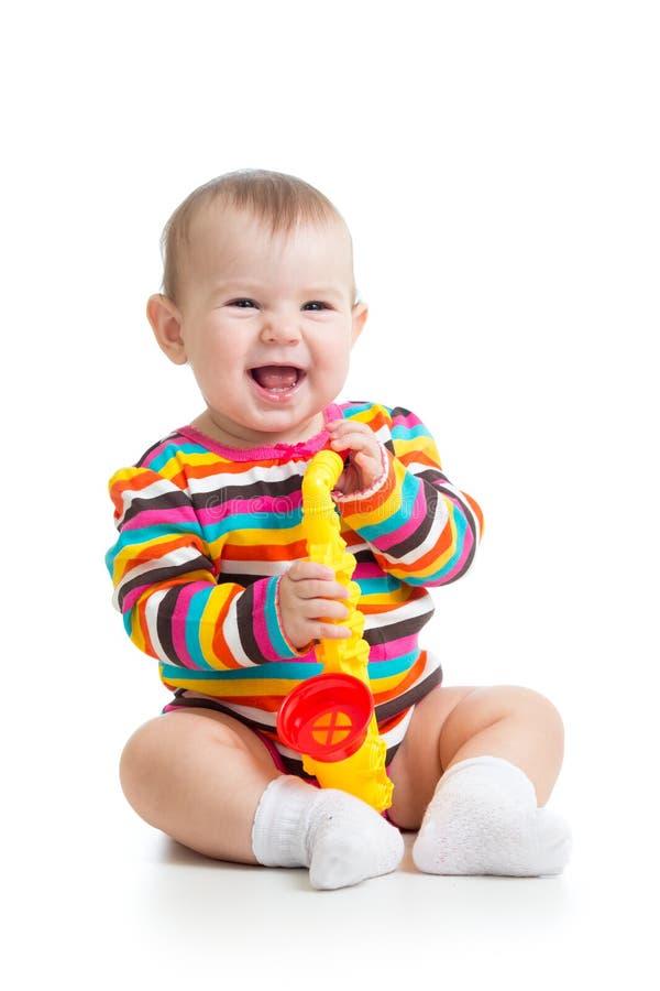Bebé divertido con el juguete musical aislado fotografía de archivo