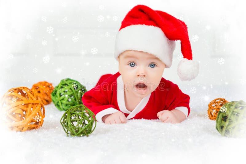 Bebé divertido de la Navidad en el traje de Santa Claus que miente en el fondo blanco fotografía de archivo