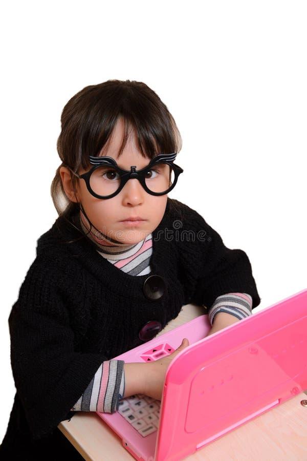 Bebé divertido detrás del ordenador portátil con los vidrios fotografía de archivo
