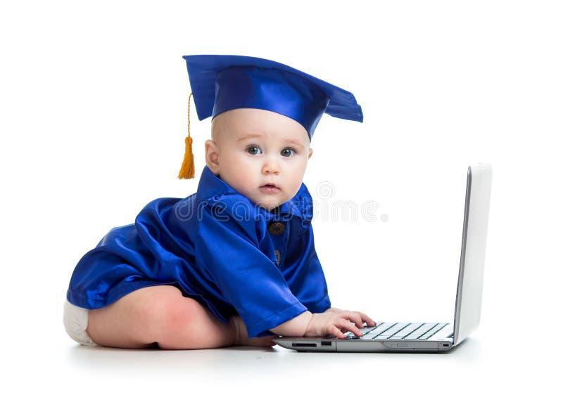 Bebé divertido en ropa del académico usando el ordenador portátil fotos de archivo libres de regalías
