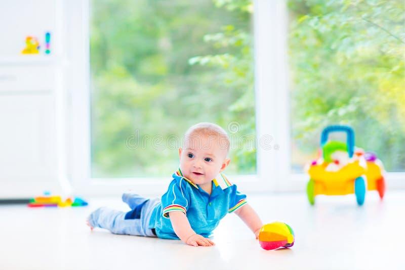 Bebé divertido que juega con el coche colorido de la bola y del juguete imagen de archivo libre de regalías
