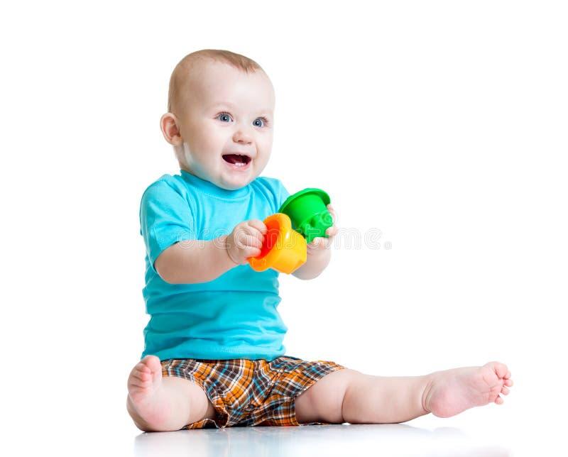 Bebé divertido que juega con los juguetes coloridos de la taza foto de archivo libre de regalías