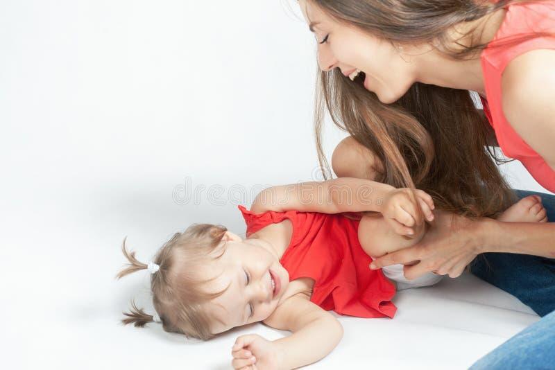 Bebé divertido que miente cerca de madre feliz en la cama blanca fotografía de archivo
