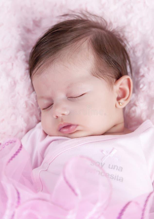 Bebé dormido en cama rosada Recién nacido Ropa rosada fotos de archivo libres de regalías