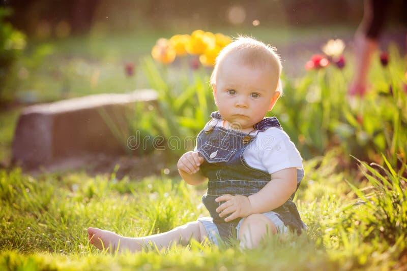 Bebé dulce del niño con su pequeño conejito, sentándose en parque, s fotos de archivo libres de regalías