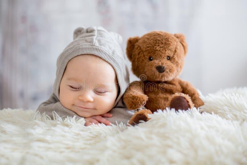 Bebé dulce en el oso total, durmiendo en cama con el oso de peluche fotos de archivo