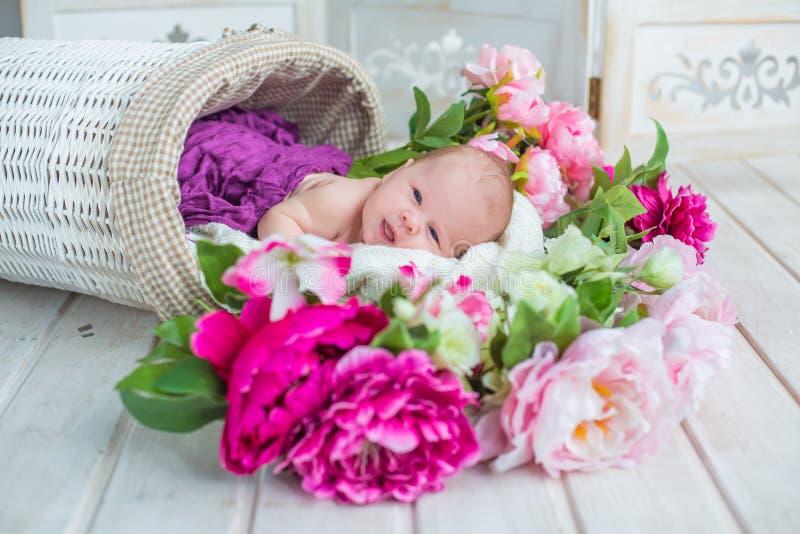 Bebé dulce lindo adorable en la cesta blanca con las flores en piso de madera fotografía de archivo libre de regalías