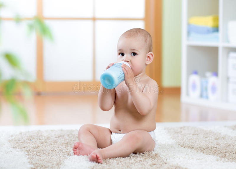 Bebé dulce que sostiene la botella y la leche de consumo imagen de archivo