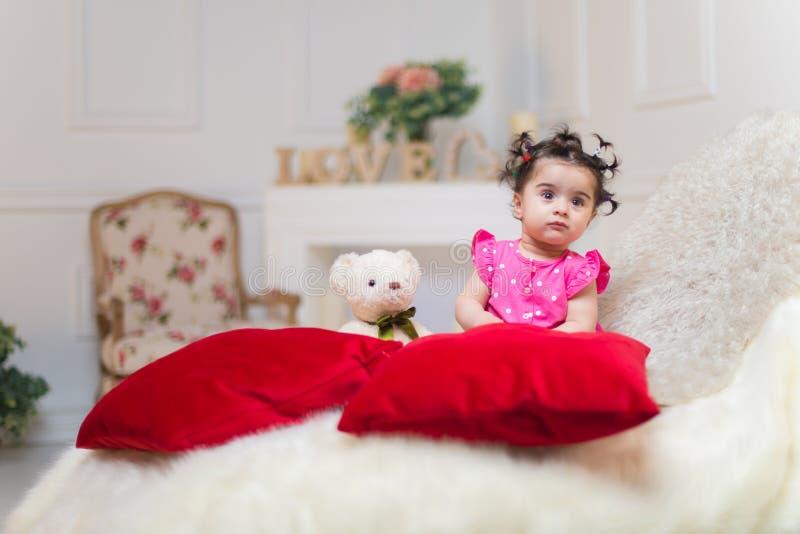Bebé dulce sonriente feliz que se sienta en el sofá con el juguete del oso foto de archivo