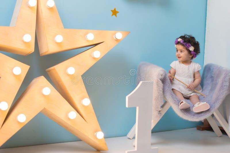 Bebé dulce sonriente feliz que se sienta en la butaca con el brillo de la estrella ligera, muchacha del cumpleaños, de un año fotos de archivo