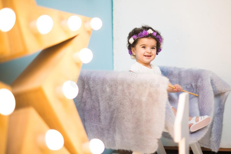 Bebé dulce sonriente feliz que se sienta en la butaca con el brillo de la estrella ligera, muchacha del cumpleaños, de un año fotos de archivo libres de regalías