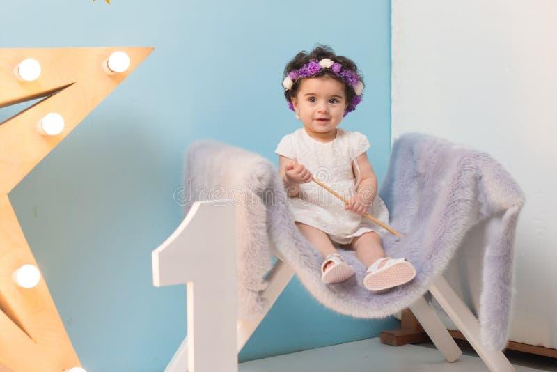 Bebé dulce sonriente feliz que se sienta en la butaca con el brillo de la estrella ligera, muchacha del cumpleaños, de un año imagen de archivo libre de regalías
