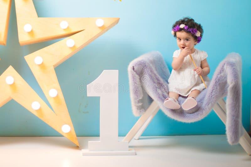 Bebé dulce sonriente feliz que se sienta en la butaca con el brillo de la estrella ligera, muchacha del cumpleaños, de un año foto de archivo