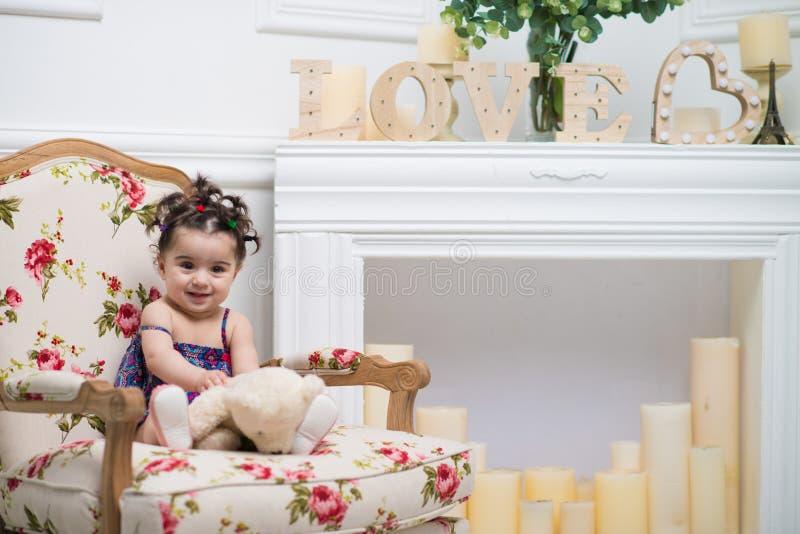 Bebé dulce sonriente feliz que se sienta en la butaca, retrato de la muchacha imagen de archivo