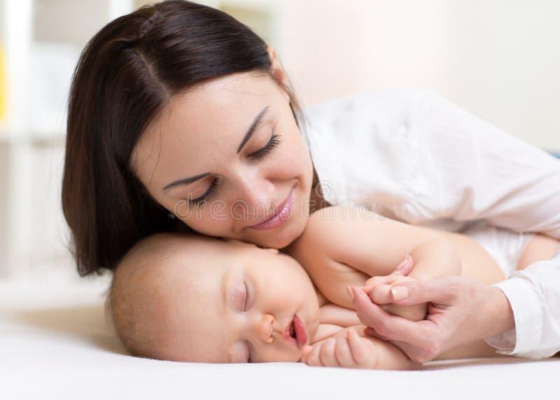 Bebé durmiente cercano de la mamá joven feliz imagenes de archivo