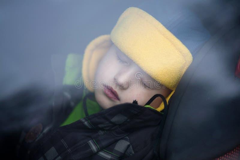 Bebé durmiente en el coche Mire a trav?s de la ventana fotos de archivo libres de regalías