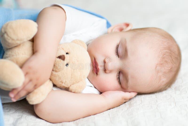 Bebé durmiente en la cama, sosteniendo un oso de peluche imágenes de archivo libres de regalías