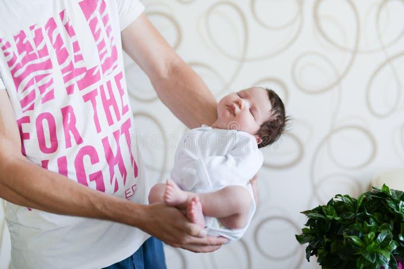 Bebé durmiente en sus brazos Padre que detiene a su hija recién nacida del bebé después de nacimiento en los brazos , Concepto de fotos de archivo