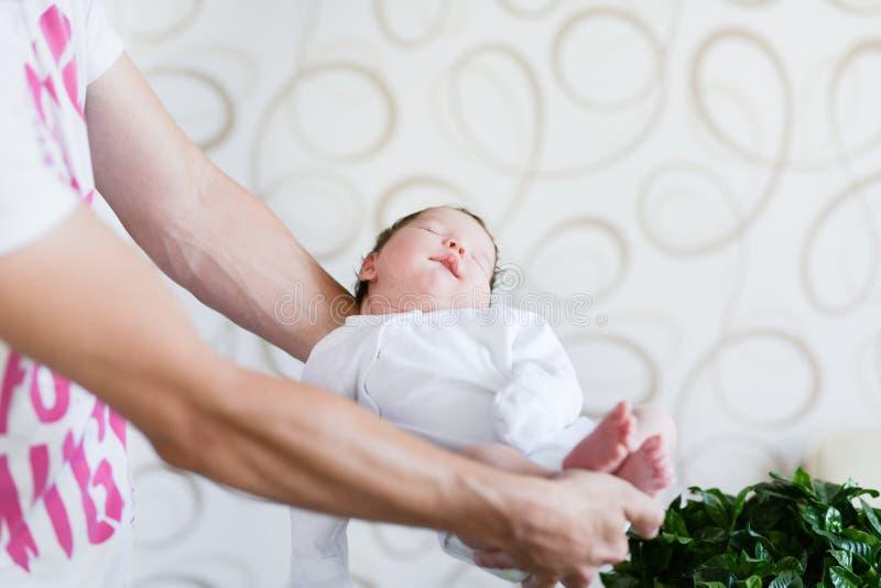 Bebé durmiente en sus brazos Padre que detiene a su hija recién nacida del bebé después de nacimiento en los brazos , Concepto de imagen de archivo libre de regalías