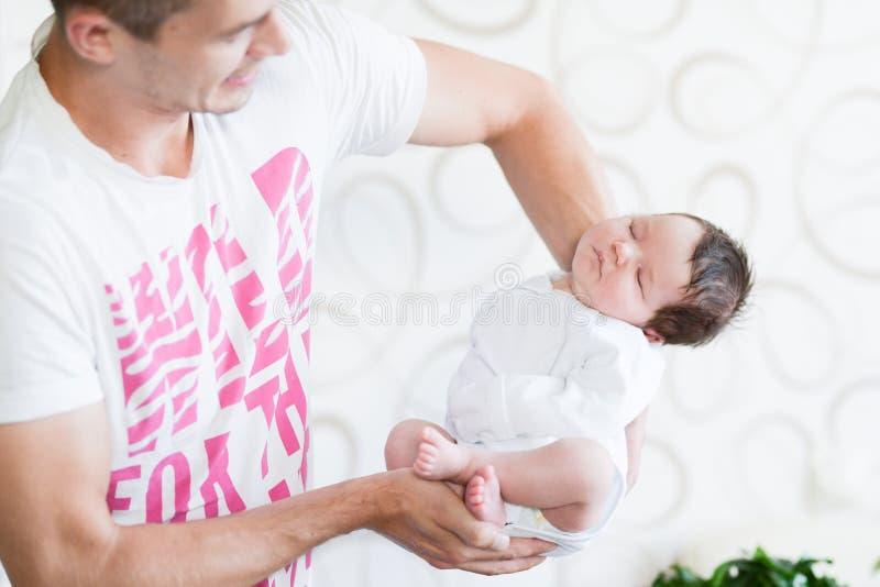 Bebé durmiente en sus brazos Padre que detiene a su hija recién nacida del bebé después de nacimiento en los brazos , Concepto de imágenes de archivo libres de regalías