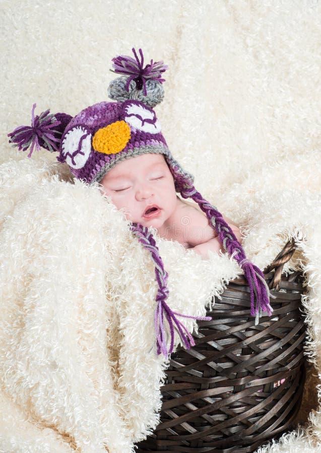 Bebé durmiente en una cesta que lleva un sombrero hecho a ganchillo del búho imágenes de archivo libres de regalías