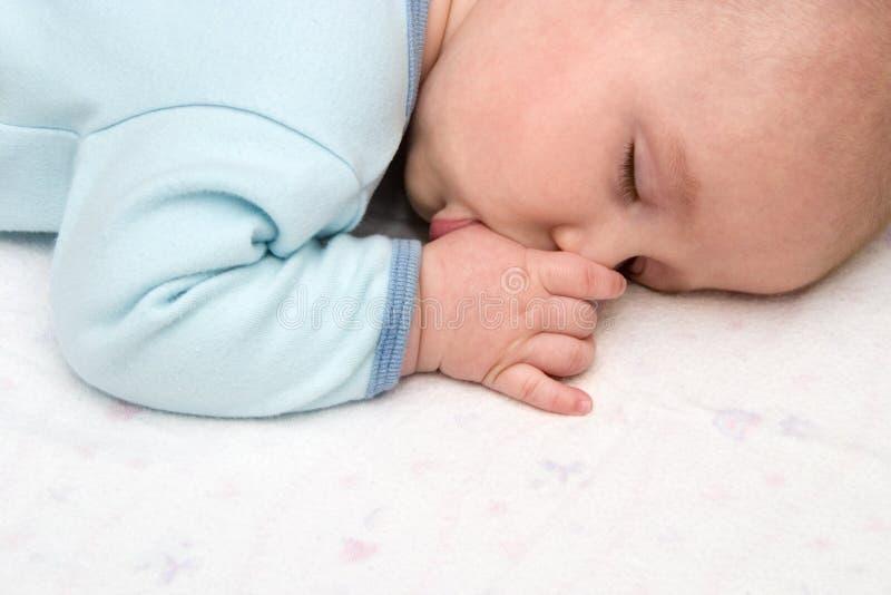 Bebé durmiente que aspira el pulgar fotografía de archivo