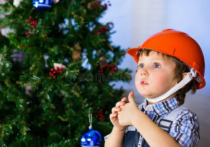 Bebé en casco de la construcción en el fondo del árbol de navidad imagen de archivo