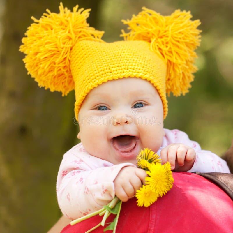 Bebé en casquillo hecho punto amarillo con los dientes de león fotografía de archivo