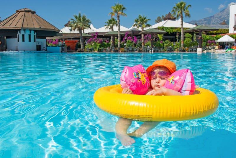 Bebé en centro turístico de la piscina del verano imagenes de archivo