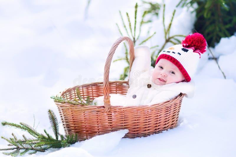 Bebé en cesta como regalo de Navidad en parque del invierno imagenes de archivo