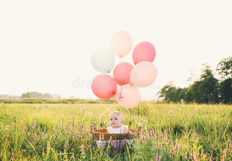 Bebé en cesta de mimbre con los globos en la naturaleza en el verano foto de archivo