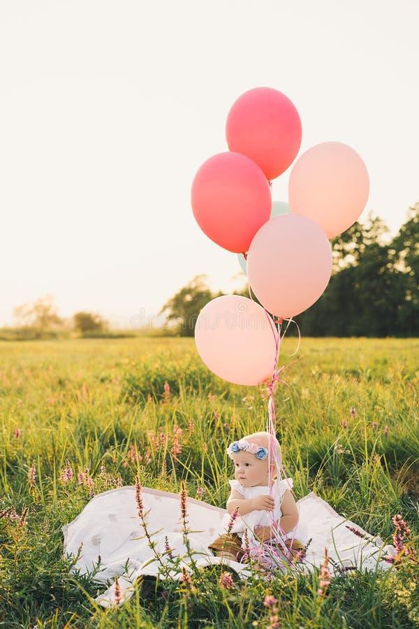 Bebé en cesta de mimbre con los globos en la naturaleza en el verano fotos de archivo