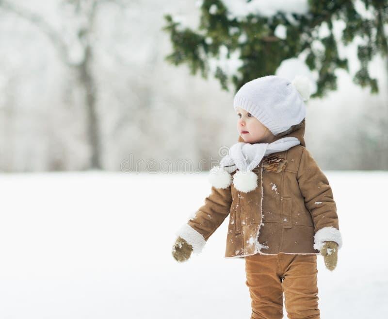 Bebé en el parque del invierno que mira en espacio de la copia imagen de archivo