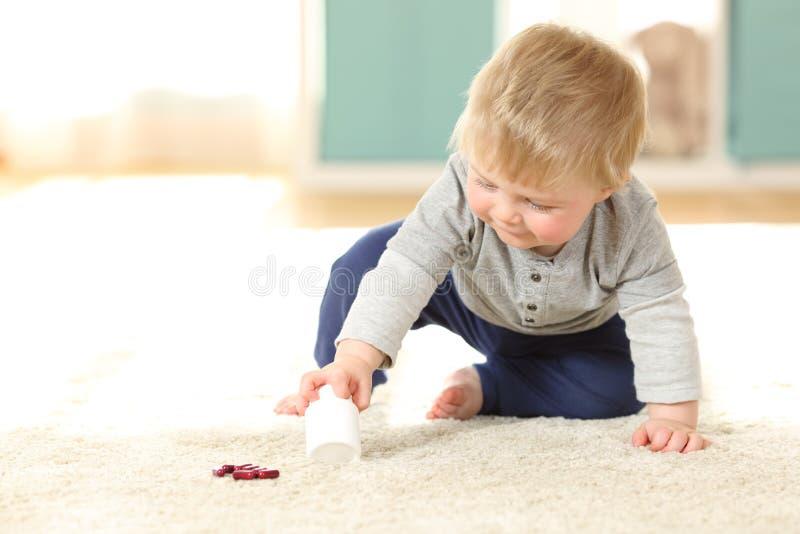 Bebé en el peligro que juega con una botella de píldoras foto de archivo libre de regalías